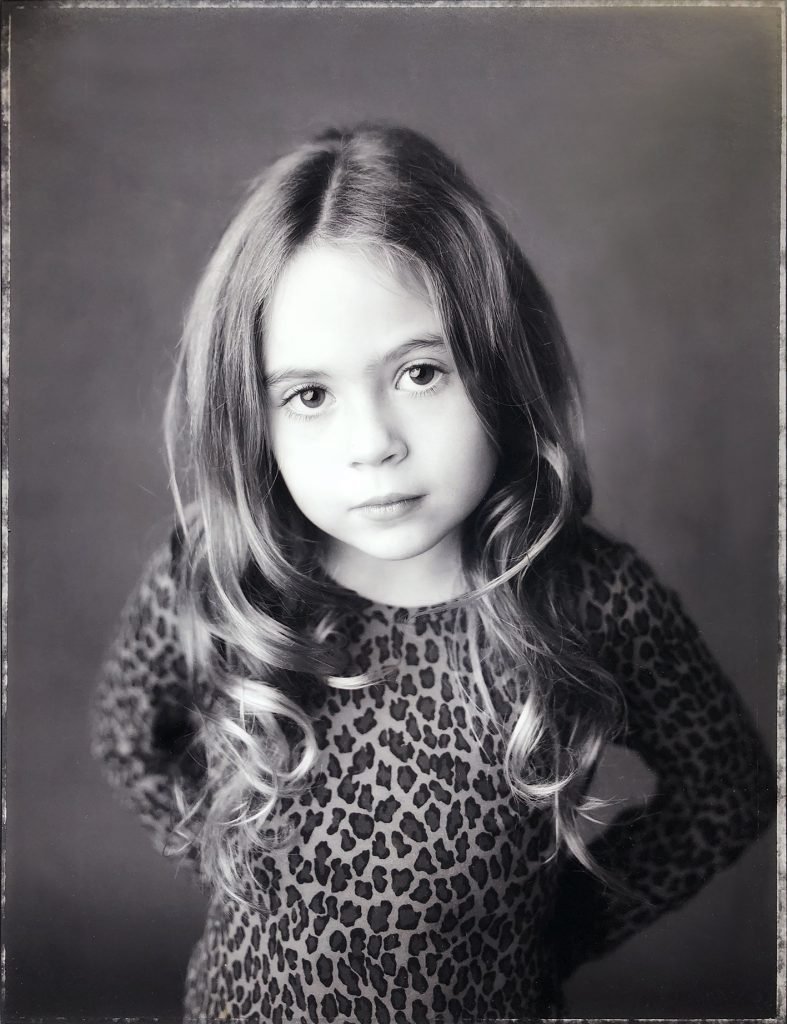 A sepia portrait of a young girl wearing a leopard pattern top
