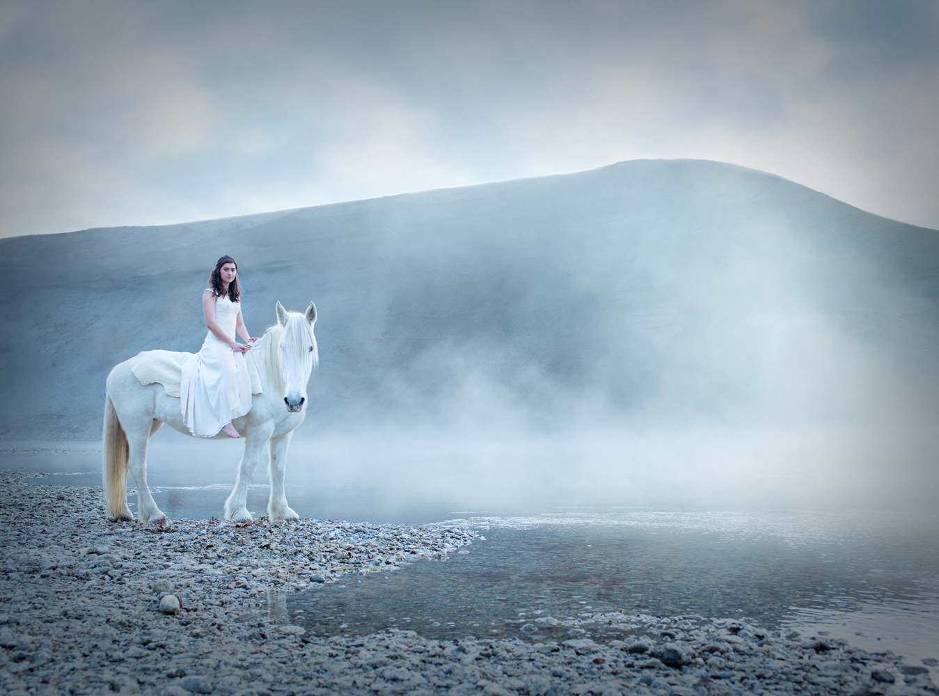 Women on a white horse wearing white dress, misty morning lake